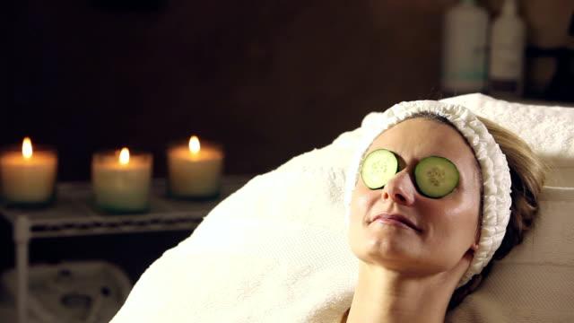 stockvideo's en b-roll-footage met vrouw krijgt spabehandeling, komkommers op ogen - spa behandeling