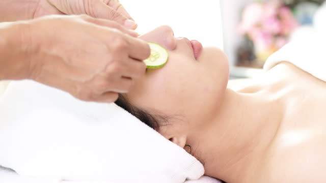 woman getting spa treatment, cucumbers on face. - facial stock videos & royalty-free footage