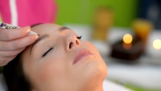 vídeos de stock e filmes b-roll de woman getting tweezing procedure - sobrancelha
