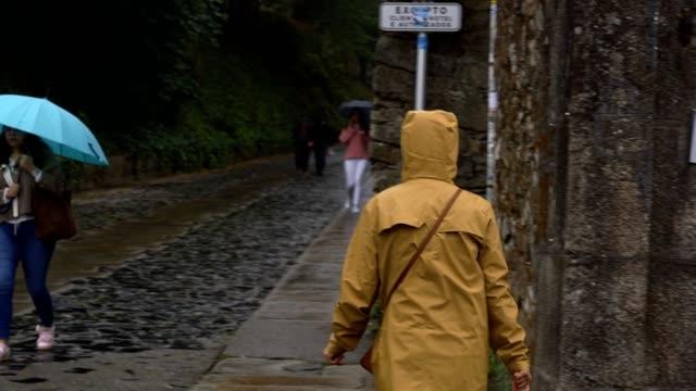 девушка-путешественница гуляет по улице дождь день с желтой курткой в сантьяго-де-компостела города, испания - жакет стоковые видео и кадры b-roll