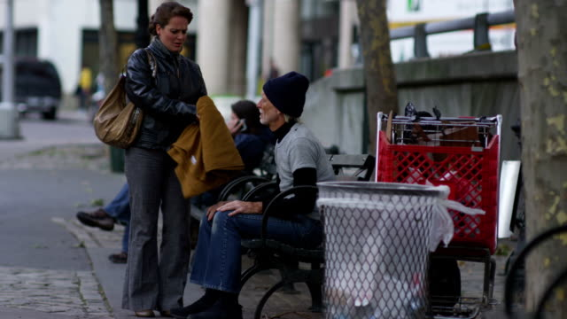 Woman gives blanket to homeless man HD 1080p: Woman gives blanket to homeless man on New York City street poverty stock videos & royalty-free footage