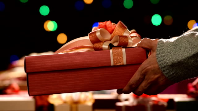 Woman giving a christmas present to a man Woman giving a christmas present to a man wrapped stock videos & royalty-free footage