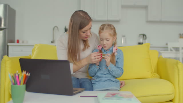 woman giving online shopping education to daughter - didattica a distanza video stock e b–roll