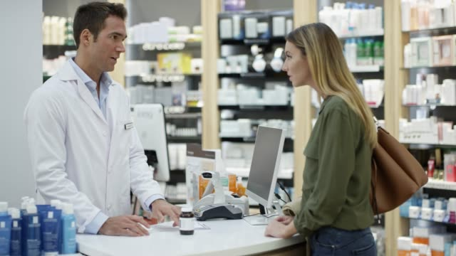 Woman giving prescription medicine to chemist Slow motion shot of chemist explaining prescription medicine to customer. Woman listening to pharmacist at checkout counter. They are in drug store. pharmacist stock videos & royalty-free footage