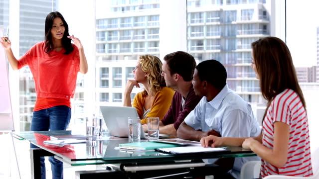 vidéos et rushes de femme donnant la présentation à ses collègues - mode bureau