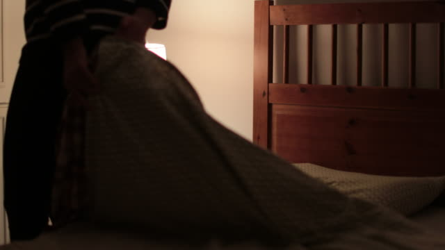 woman goes to bed and turns off night-stand lamp in 4k - bielizna nocna filmów i materiałów b-roll