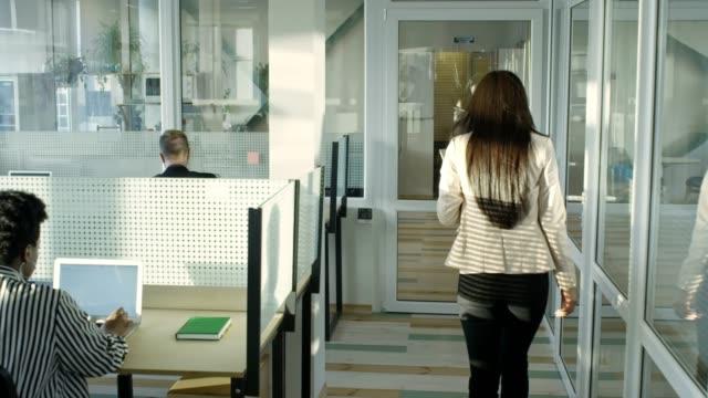 woman going through modern open space office with glass walls - odejście filmów i materiałów b-roll