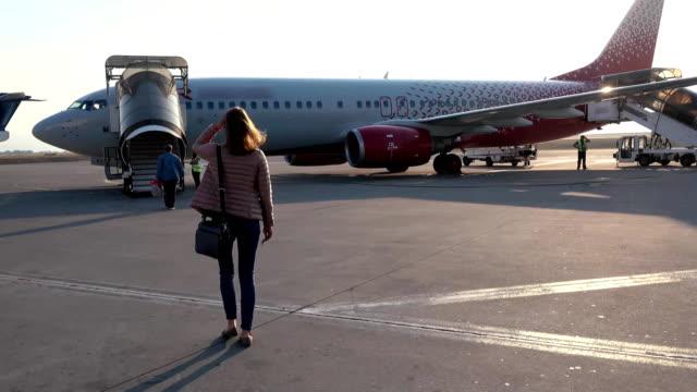 woman going to plane an aerodrome - wchodzić na pokład filmów i materiałów b-roll