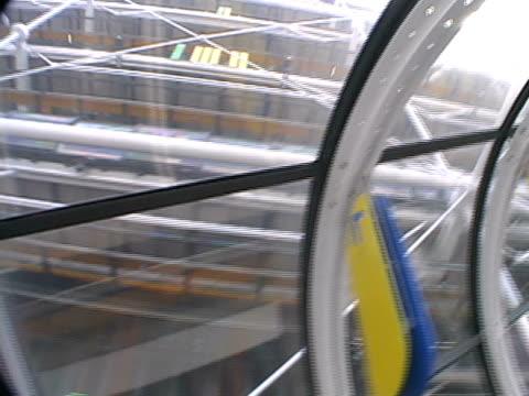 vidéos et rushes de femme va vers le haut de l'escalier roulant vitrée - une seule femme d'âge mûr