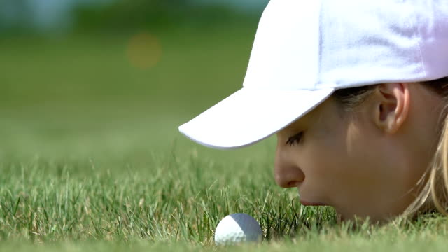 Woman golf beginner player lying on grass and blowing ball into hole, having fun