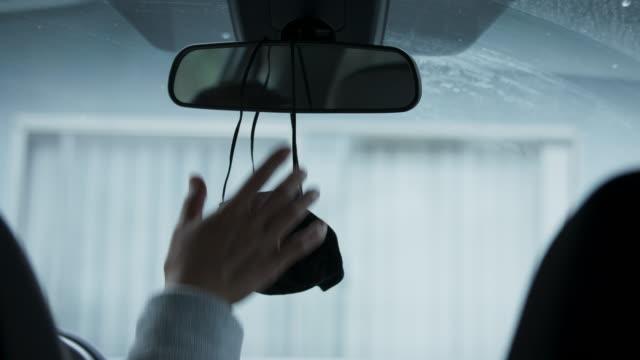 stockvideo's en b-roll-footage met vrouw die een zwart gezichtsmasker van haar achteruitkijkspiegel grijpt - mirror mask