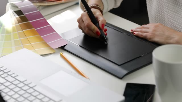 woman graphic designer using digital drawing tablet at advertising agency office video