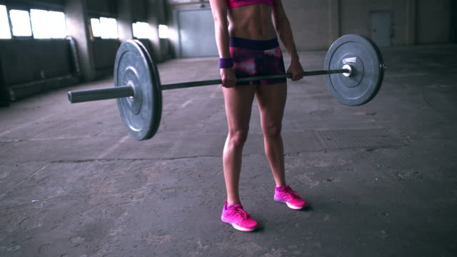 Woman gripping a barbell with heavy weights about to lift video