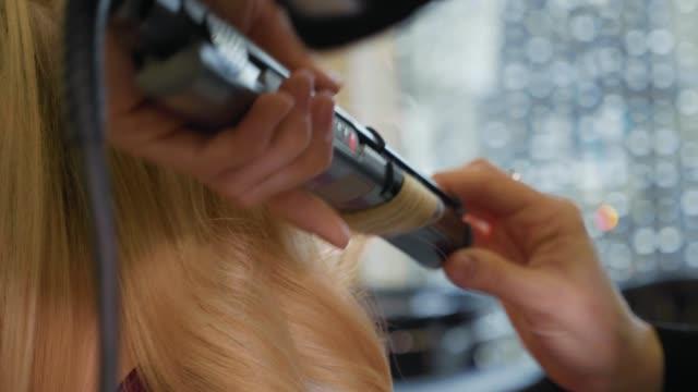 stockvideo's en b-roll-footage met vrouw kapper maken krullen bij blond haar met krultangen bij beauty salon. - blond curly hair
