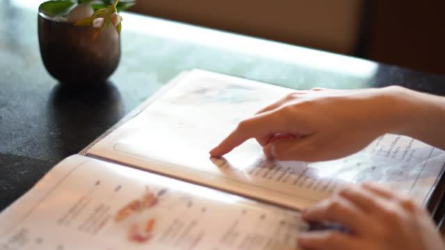 vidéos et rushes de main femme choisir menu à rendre ordonnance alimentaire pour le dîner au restaurant. - recette