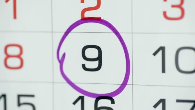 kobieta ręka koło dzień w kalendarzu papierowym. 9 dzień miesiąca - data filmów i materiałów b-roll