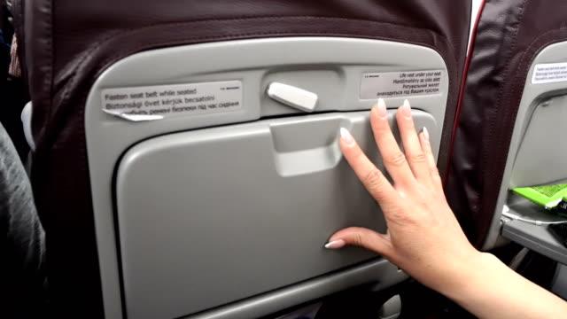 woman hand close airplane tray table - taca filmów i materiałów b-roll