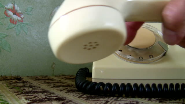 Woman hand dialing an old white telephone video