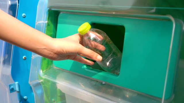 SLO MO Woman Hand droping plastic bottles in recycle bin garbage