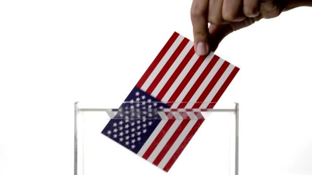 Woman hand dropping USA flag into voting ballot