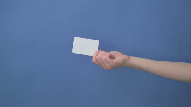 Woman hand hold business card, credit card or blank paper isolated Woman hand hold business card, credit card or blank paper isolated on blue background. business card stock videos & royalty-free footage