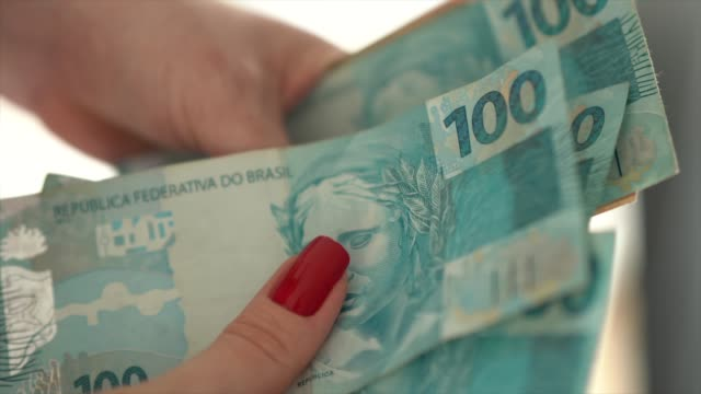 Woman hand holding a the currency of reais, brazilian money Counting my money paper currency stock videos & royalty-free footage