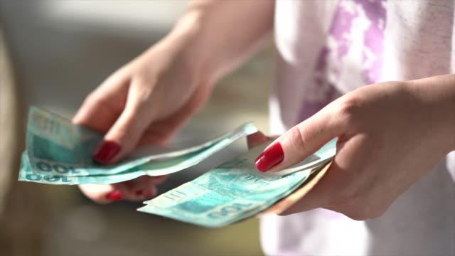 kvinna hand innehav en valuta reais, brasilianska pengar - lön bildbanksvideor och videomaterial från bakom kulisserna