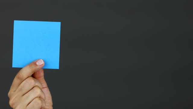 Woman hand holding blank blue stick note