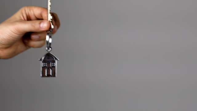 woman hand, holding keys of a new home, enters into the camera frame and shows key and key ring of a new home - key ring stock videos & royalty-free footage