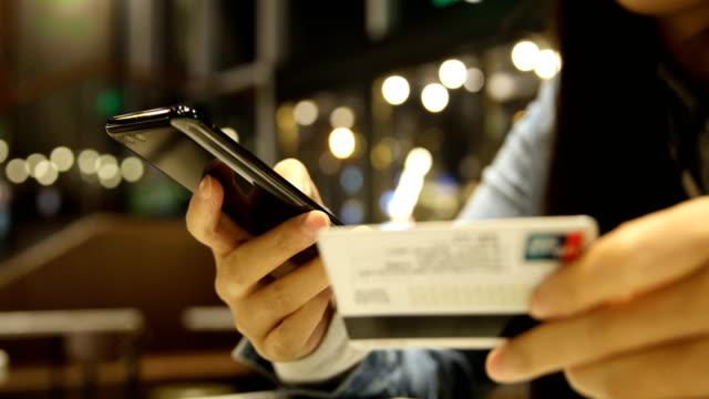 携帯電話やクレジット カードのオンライン ショッピングを持つ女性の手 - オンラインショッピング点の映像素材/bロール