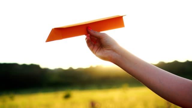 vídeos de stock, filmes e b-roll de mulher segurando avião de papel ao pôr do sol laranja. conceito de liberdade - braço humano