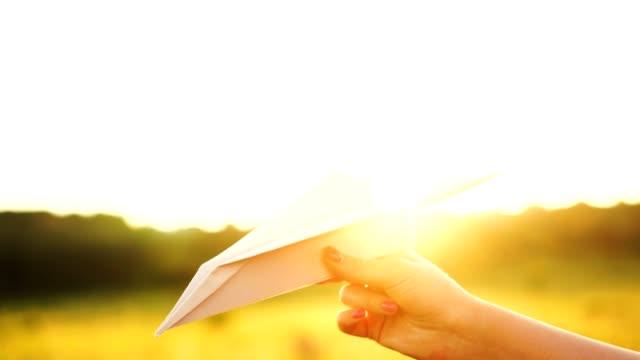 vídeos de stock, filmes e b-roll de mulher segurando plano de papel branco ao pôr do sol laranja. conceito de liberdade - braço humano