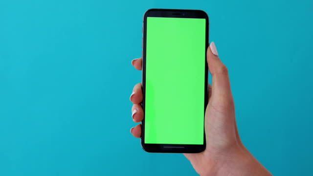 Woman hand holds a smartphone with greeen screen