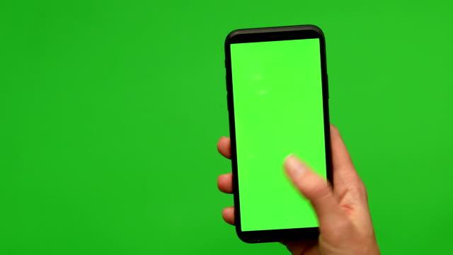 女人手拿著一個智慧手機與格林螢幕 - 握住 個影片檔及 b 捲影像