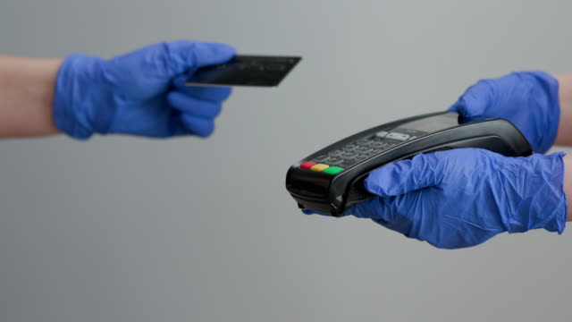 vídeos de stock e filmes b-roll de woman hand in gloves with credit card swipe through pos terminal and enter pin code. banking services of electronic money. financial success and safety. credit card machine for money transaction - paying with card contactless