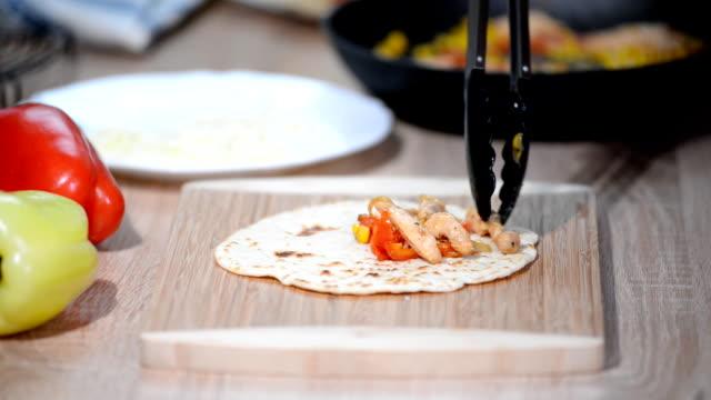 vidéos et rushes de la main de femme fait la maison traditionnelle mexicaine burrito de nourriture. - emballé