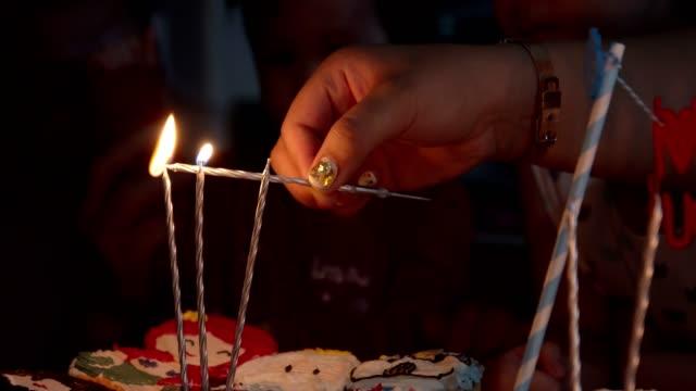 CU : Woman hand lighting candles on birthday cake