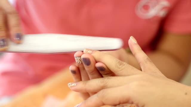 vidéos et rushes de femme main de manucure en salon de beauté - ongle
