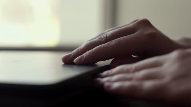 Woman hand opens the lid of a laptop close up near the window in slow motion