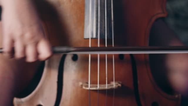 woman hand playing violoncello with cello bow. cello playing music background - orchestra video stock e b–roll