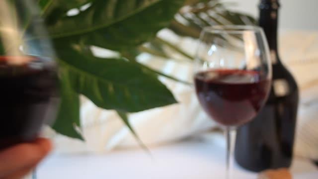 frau hand legte ein glas mit rotweinroten wein. flasche auf dem hintergrund. romantisches dinner-konzept - cabernet sauvignon traube stock-videos und b-roll-filmmaterial