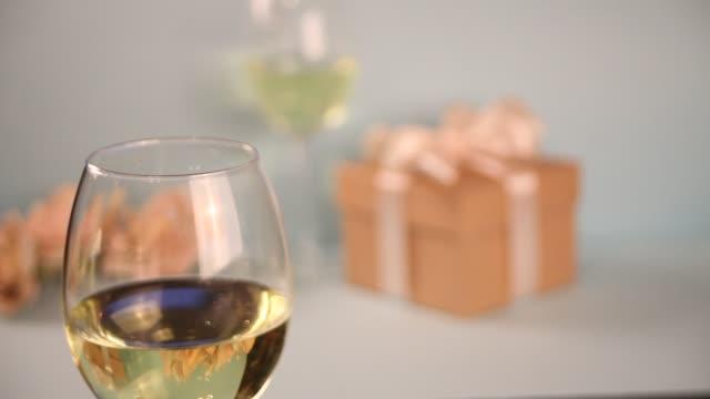 frau hand legte ein glas mit weißen traubenwein. geschenk-box auf dem hintergrund. romantisches dinner-konzept - cabernet sauvignon traube stock-videos und b-roll-filmmaterial