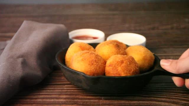 vídeos de stock, filmes e b-roll de mão de mulher colocar uma panela com bolas de croquetes de batata na mesa de madeira. - comida salgada
