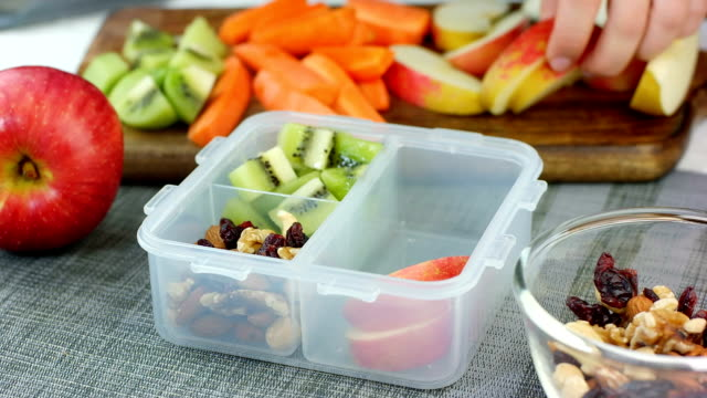 Woman hand put healthy fruit and nut snacks into the lunch box and close it Woman hand put healthy fruit and nut snacks into the lunch box and close it healthy lifestyle stock videos & royalty-free footage