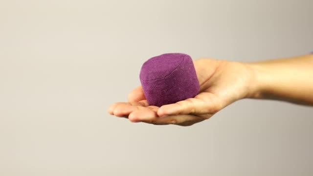 vídeos y material grabado en eventos de stock de una mano de mujer muestra la bola de la púrpura de la tensión y comienza a apretar y soltarlo - estrujar