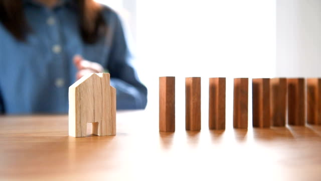 vídeos de stock e filmes b-roll de woman hand stopping risk the wooden blocks from falling on house. - continuidade
