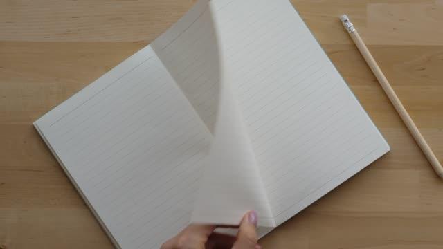 Mão de mulher swing limpas páginas no caderno - vídeo