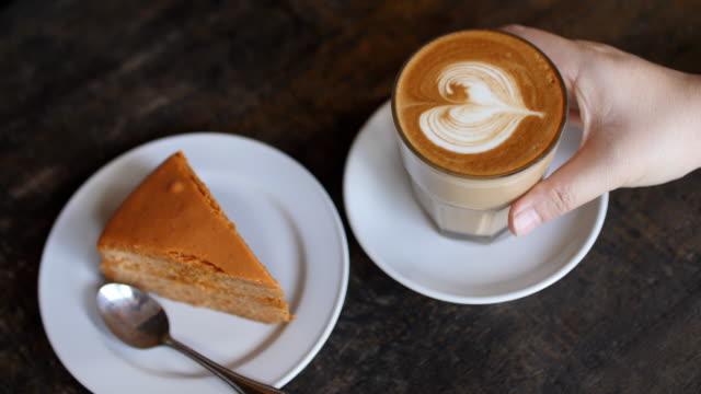 vídeos de stock e filmes b-roll de woman hand take a coffee with cake in coffee cafe , slow motion - bebida com espuma