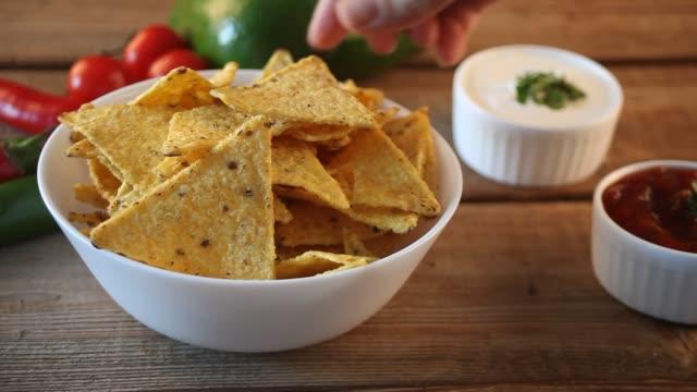 kvinnan hand tar mexikanska chips nachos och dips i en sås salsa - chips bildbanksvideor och videomaterial från bakom kulisserna