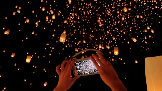 Woman hand taking sky lantern picture with Smart Phone video